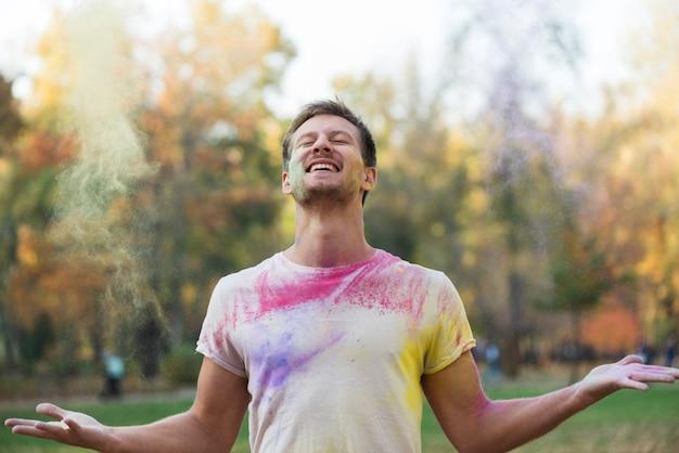 Lächelnder mann, der holi festival genießt