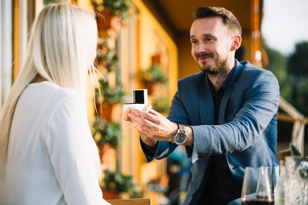 Lächelnder mann, der ihre freundin vorschlägt, indem sie verlobungsring gibt