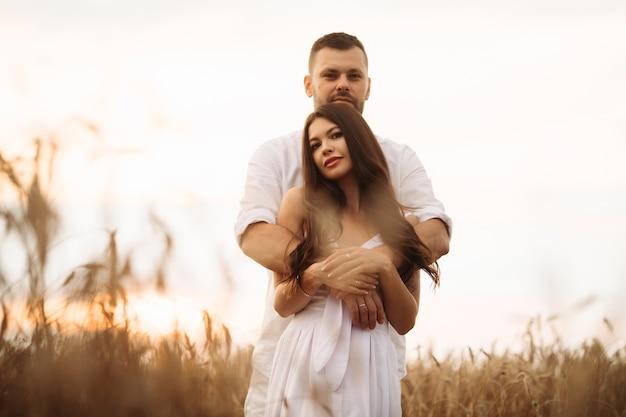 Lächelnder mann, der ihre hübsche frau umarmt, während hinter ihr auf einem weizenfeld während des abendlichen sonnenuntergangs steht. liebeskonzept