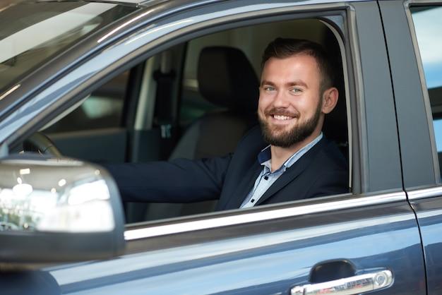 Lächelnder mann, der in der autokabine, kamera betrachtend sitzt.