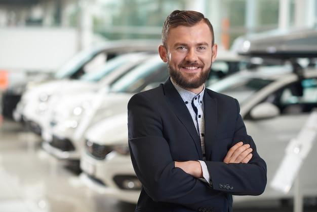 Lächelnder mann, der in der modernen automitte und -aufstellung steht.