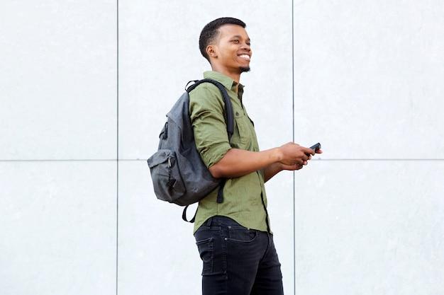 Lächelnder mann, der intelligentes telefon mit rucksack hält