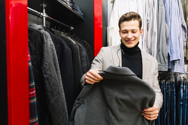 Lächelnder mann, der jacke in einem shop wählt