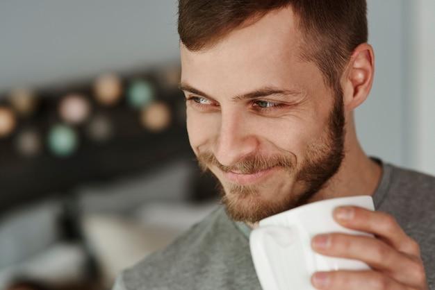 Lächelnder mann, der kaffee im schlafzimmer trinkt