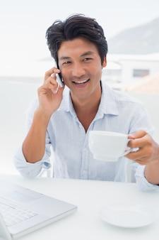 Lächelnder mann, der kaffee trinkt und am telefon spricht