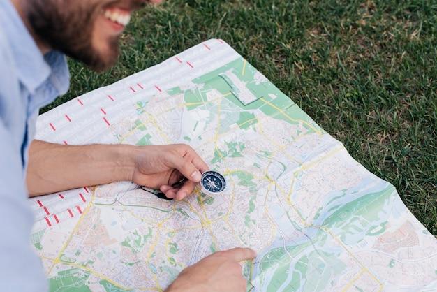 Lächelnder mann, der kompass hält und auf karte auf gras zeigt