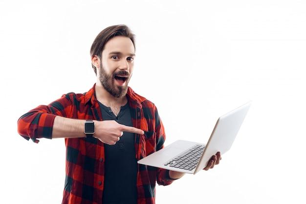 Lächelnder mann, der laptop hält und auf ihn zeigt