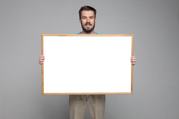 Lächelnder mann, der leeres weißes brett zeigt