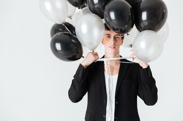 Lächelnder mann, der luftballons hält