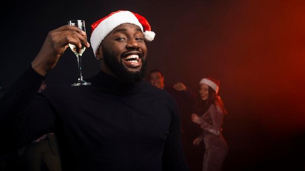 Lächelnder mann, der mit champagnerglas für neue jahre zujubelt