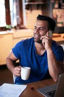 Lächelnder mann, der mit dem handy spricht und kaffee trinkt