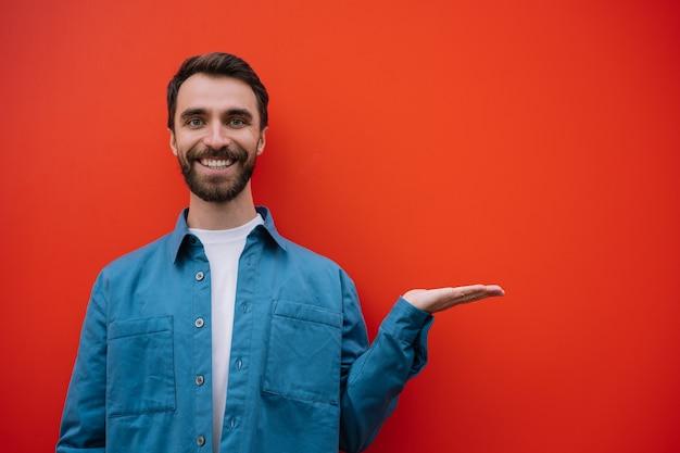 Lächelnder mann, der mit der hand zeigt, lokalisiert auf rotem hintergrund. kopierfläche, werbekonzept