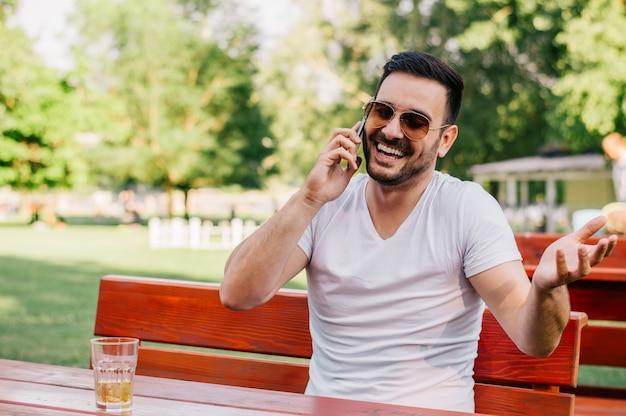 Lächelnder mann, der mit freunden am handy beim sitzen im café spricht.