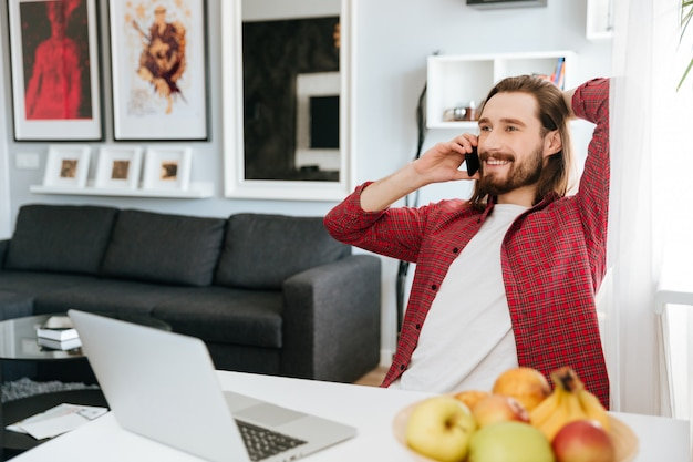 Lächelnder mann, der mit laptop arbeitet und auf handy spricht