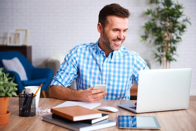 Lächelnder mann, der mit laptop arbeitet