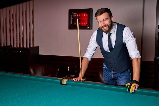 Lächelnder mann, der neben billardtisch steht, kamera betrachtet, posiert, in formeller kleidung. porträt
