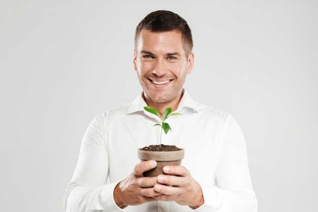 Lächelnder mann, der pflanze hält.