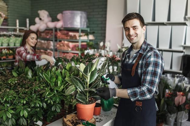 Lächelnder mann, der pflanzen im gartencenter besprüht