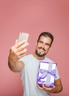 Lächelnder mann, der purpurrote geschenkbox selfie vom mobiltelefon nehmend hält