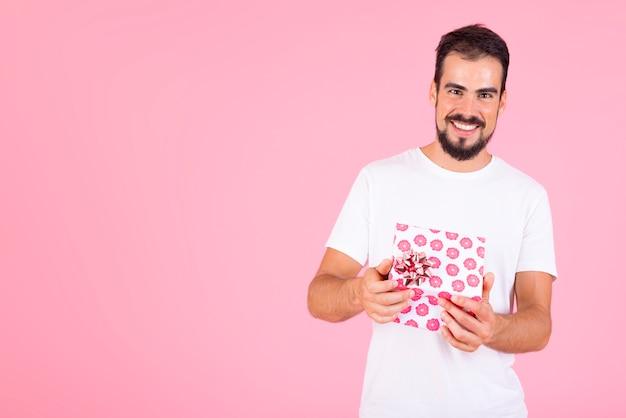 Lächelnder mann, der rosa blumengeschenkbox gegen rosa hintergrund hält