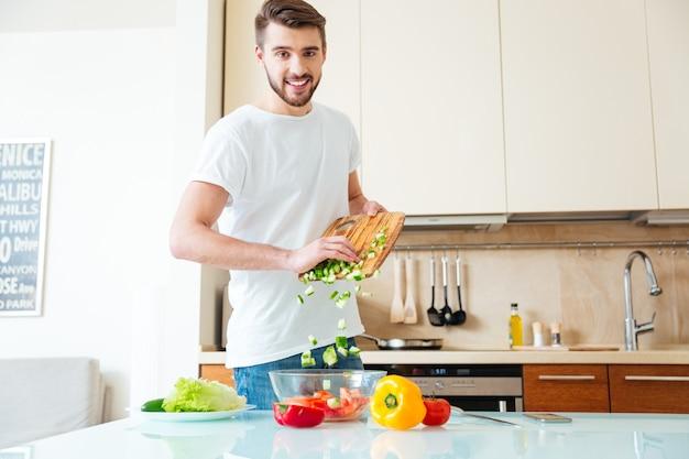 Lächelnder mann, der salat in der küche zubereitet