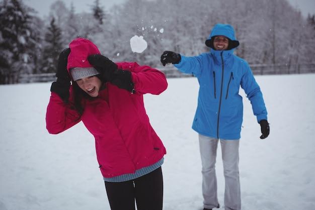 Lächelnder mann, der schneeball auf frau wirft