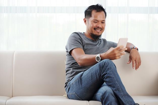 Lächelnder mann, der sein telefon überprüft
