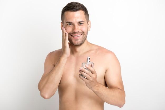 Lächelnder mann, der seine backe beim halten der aftershavelotionsflasche berührt