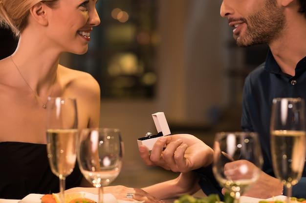 Lächelnder mann, der seine freundin im restaurant vorschlägt.