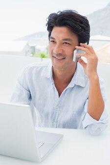 Lächelnder mann, der seinen laptop verwendet und am telefon spricht