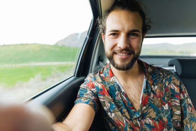Lächelnder mann, der selfie im auto nimmt