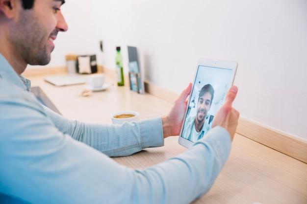 Lächelnder mann, der selfie mit tablette nimmt