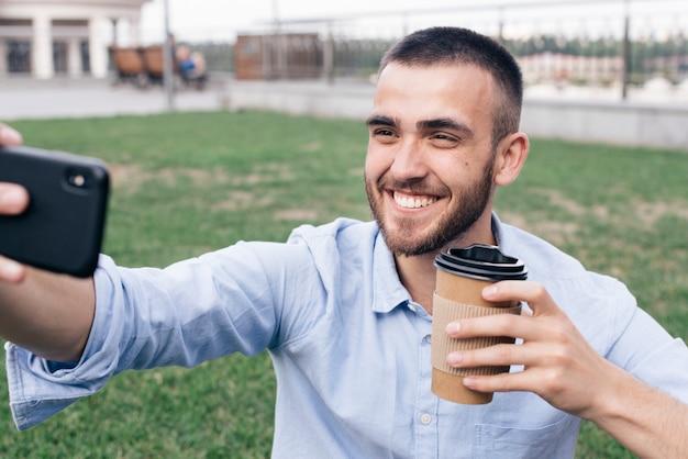 Lächelnder mann, der selfie nimmt, während er wegwerfkaffeetasse am park hält