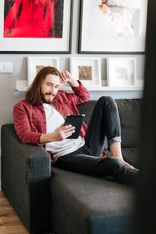 Lächelnder mann, der sitzt und tablette auf couch zu hause benutzt