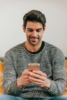Lächelnder mann, der smartphone durchstöbert