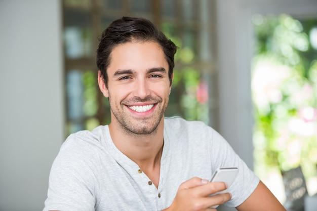 Lächelnder mann, der smartphone hält