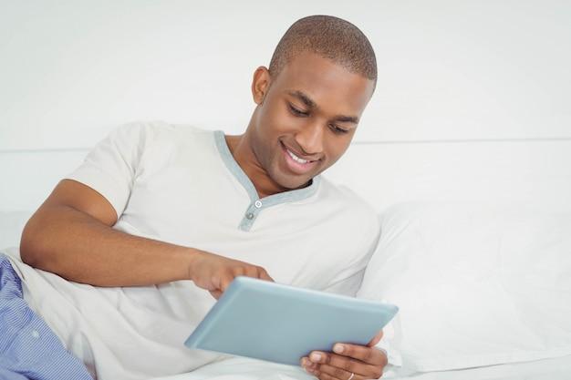 Lächelnder mann, der tablette auf dem bett verwendet