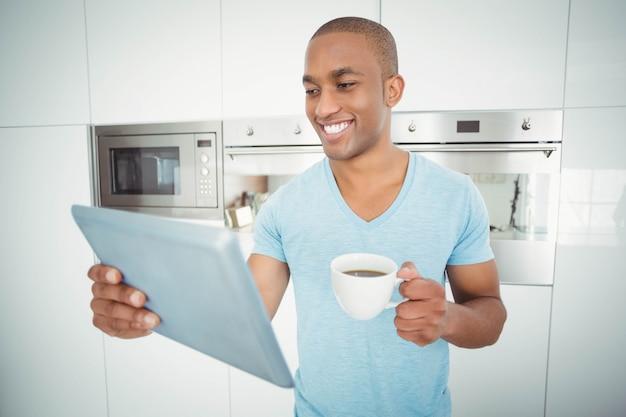 Lächelnder mann, der tablette verwendet und kaffee in der küche hält