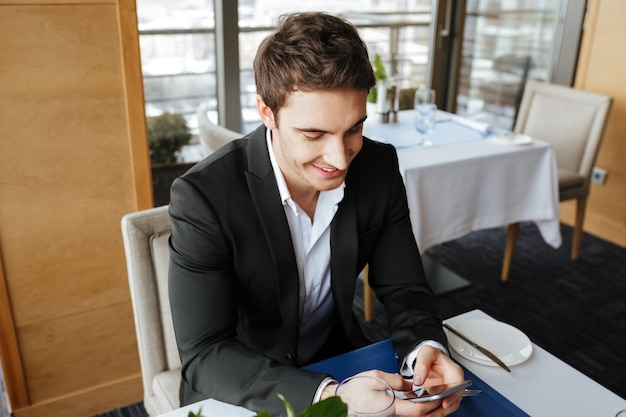 Lächelnder mann, der telefon im restaurant benutzt
