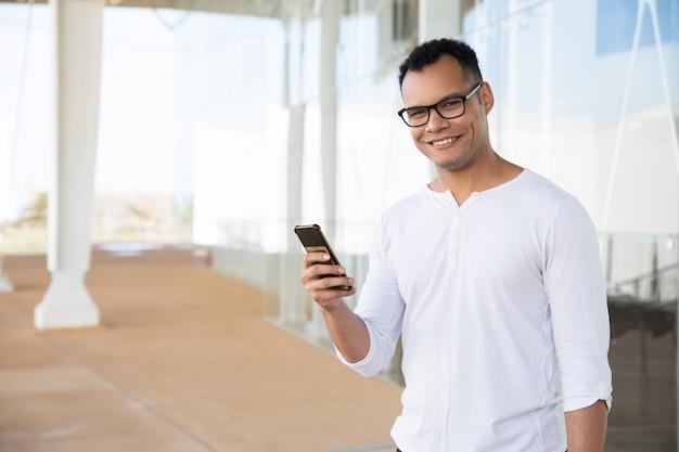 Lächelnder mann, der telefon in den händen, kopf zur kamera drehend hält