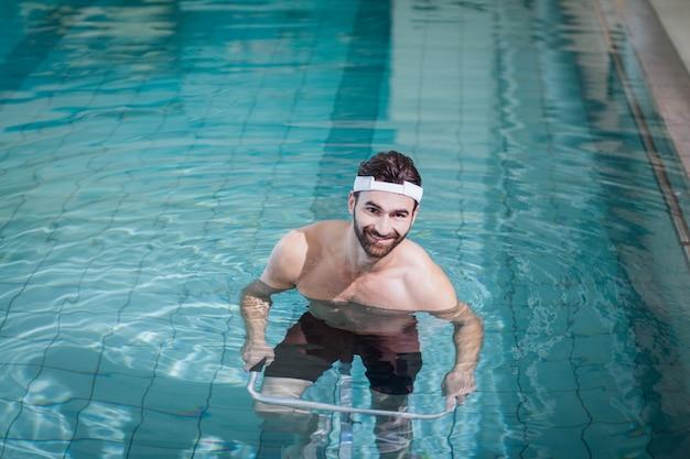 Lächelnder mann, der unterwasserfahrrad im pool tut
