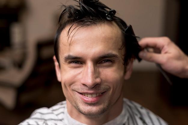 Lächelnder mann der vorderansicht am friseursalon
