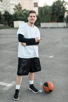 Lächelnder mann der vorderansicht mit einem basketball