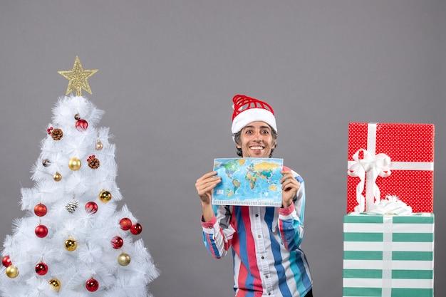 Lächelnder mann der vorderansicht mit spiralfeder-weihnachtsmannmütze, die weltkarte mit beiden händen hält