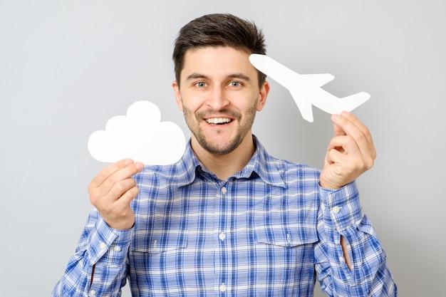 Lächelnder mann, der weißes papiermodell des flugzeugs und der wolke hält