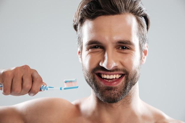 Lächelnder mann, der zähne putzt