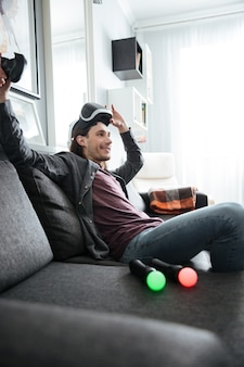 Lächelnder mann, der zu hause drinnen sitzt, spielt spiele