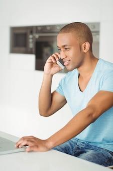 Lächelnder mann, der zu hause laptop im wohnzimmer nennt und verwendet