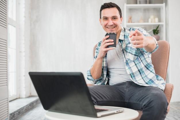 Lächelnder mann, der zu hause tasse getränk auf stuhl nahe laptop hält