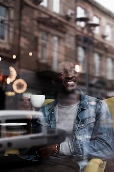 Lächelnder mann, der zuhause kaffee genießt